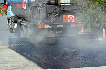 Tar truck vehicle tarring a piece of new road