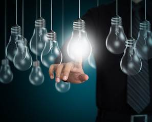 Businessman hand pointing at light bulb, Idea concept
