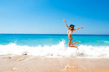 Cute brunette woman jump at sea