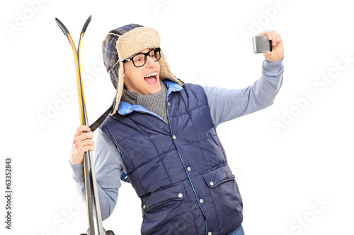 Man in winter clothes taking a selfie with skis