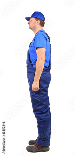 Worker in blue overalls. Side view.