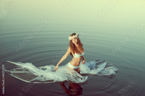 Beautiful woman in a lake at night. Girl at sunset in the lake.
