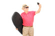 Mature man holding a surfboard and taking selfie