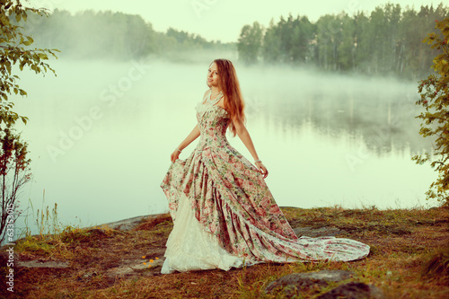 Luxury woman in a forest in a long vintage dress near the lake.