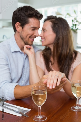 Woman showing engagement ring besides man