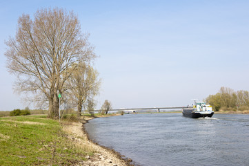 Cargo ship on river in rural scenery