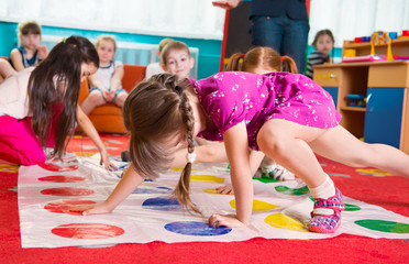 Cute toddlers playing in twister game