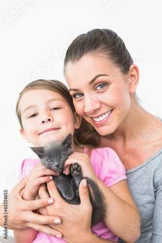 Smiling mother and daughter sitting with pet kitten together