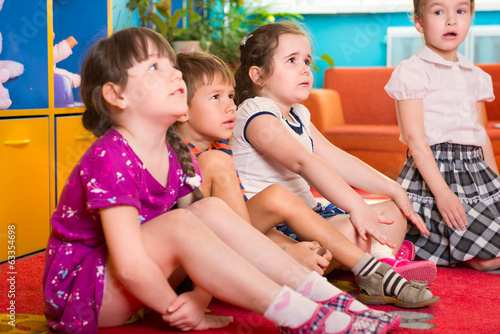 Cute preschoolers sitting on floor and listening