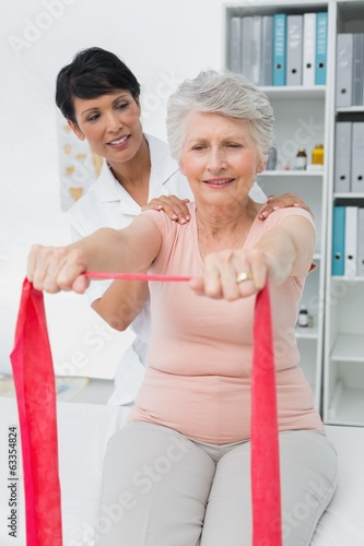 Female physiotherapist massaging senior womans back