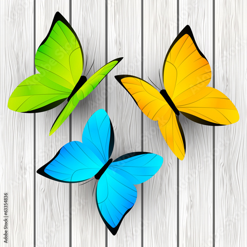 Color butterflies on wooden background