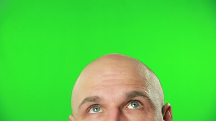 Close up of male head and eyes against a green screen
