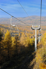Chair lift with pillars against autumn mountain forest