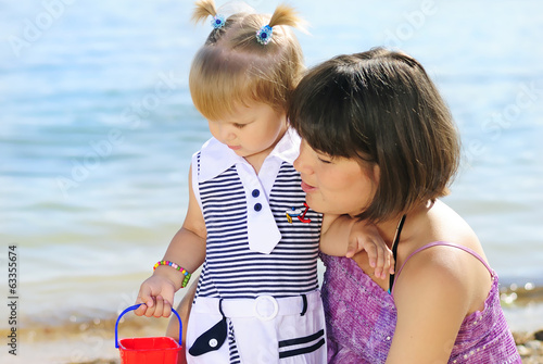 little girl with her mother on the shore of the sea in the summe