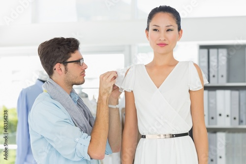 Fashion designer adjusting dress on model