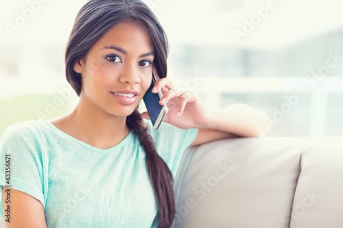 Smiling girl sitting on sofa making a phone call