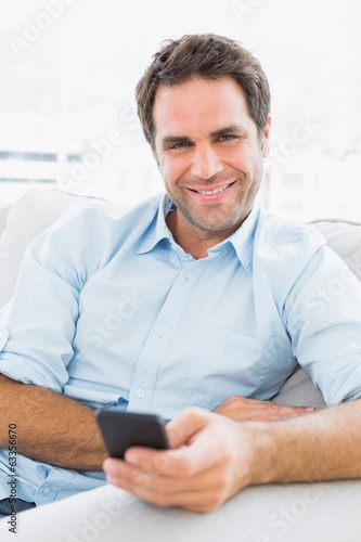 Cheerful man sitting on the couch sending a text
