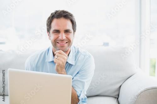 Happy man using laptop smiling at camera