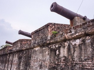 A row of old cannon guns atop a fort