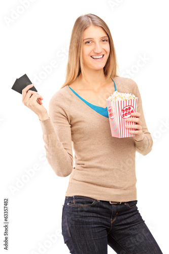 Girl holding two movie tickets and box of popcorn