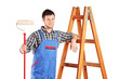 Male painter standing next to a ladder