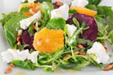 fresh salad with roasted beetroot, white cheese, orange, and pin