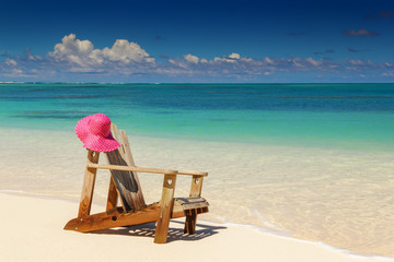 Beach chairs with pink hat  on white sandy beach