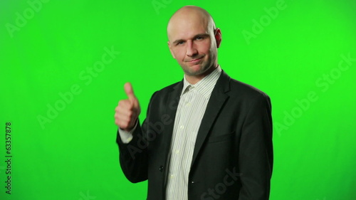Handsome businessman with thumbs up against a green screen