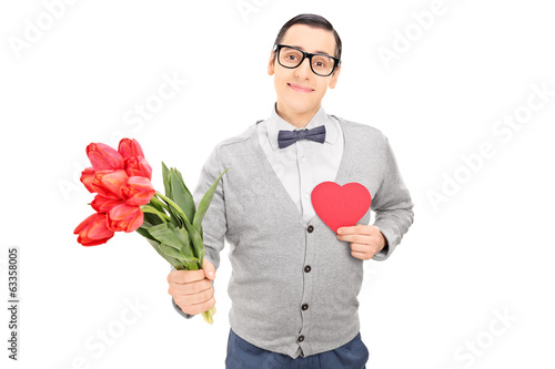 Thoughtful guy holding a red heart and flowers