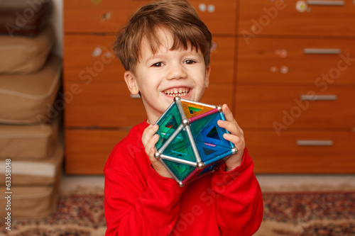 Happy skillful little boy holding toy