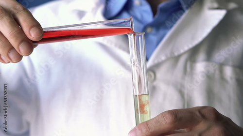 Chemist mixing chemicals in test tubes, super slow motion
