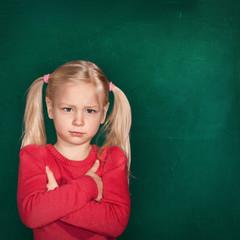 Mädchen schmollt vor Schultafel