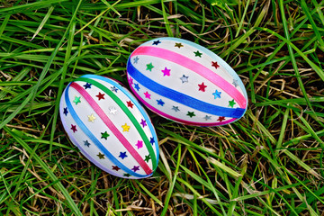 Easter eggs with ribbons and sequins on grass