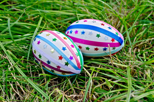 Easter eggs with ribbons and stars on grass