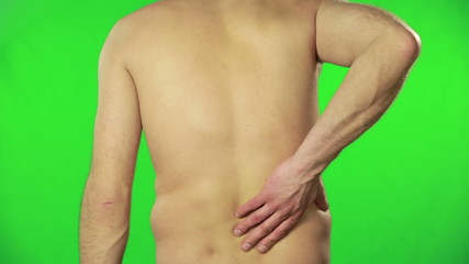 Man with back pain against a green screen