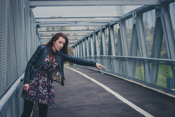 Pretty girl with long hair hitchhiking on a bridge
