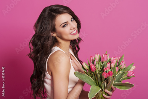 Gorgeous woman is grateful for spring bouquet