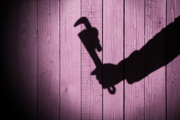 Human hand shadow with adjustable wrench  on the wood background