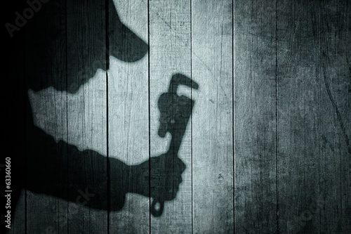 Shadow of a man with wrench  on natural wooden background