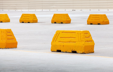 Yellow concrete road barriers on large outdoor parking area