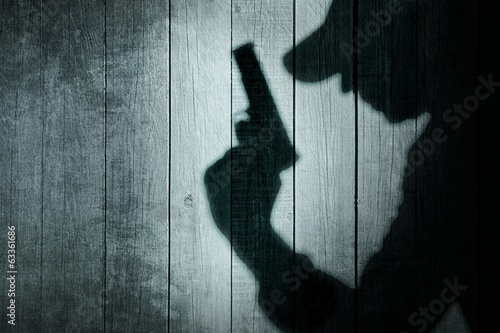 Man with a gun in shadow on a wooden background