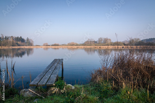 Wooden pier on the pond - romantic morning in the countryside