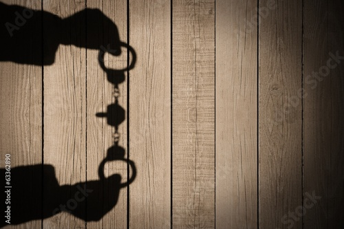 Human Hands Shadow with Handcuffs on Natural Wooden Backround, X