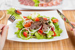Vegetable salad with beef meat and persons hands with fork and t
