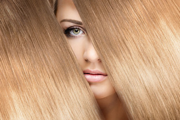 girl look through shining shiny blonde hair
