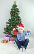 Little boy with gifts near Christmas tree in room