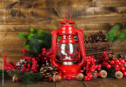 Red kerosene lamp on wooden table on wooden background