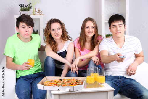 Group of young friends watching television at home