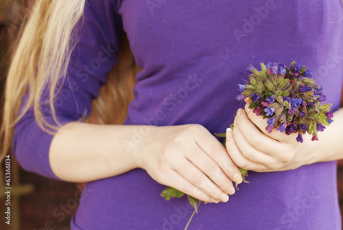Young woman holding a bouquet of wildflowers