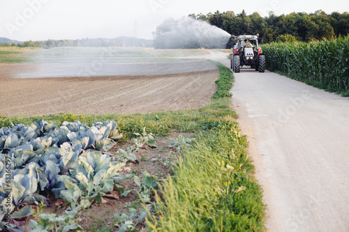 Farmer watering the field using tractor and cistern